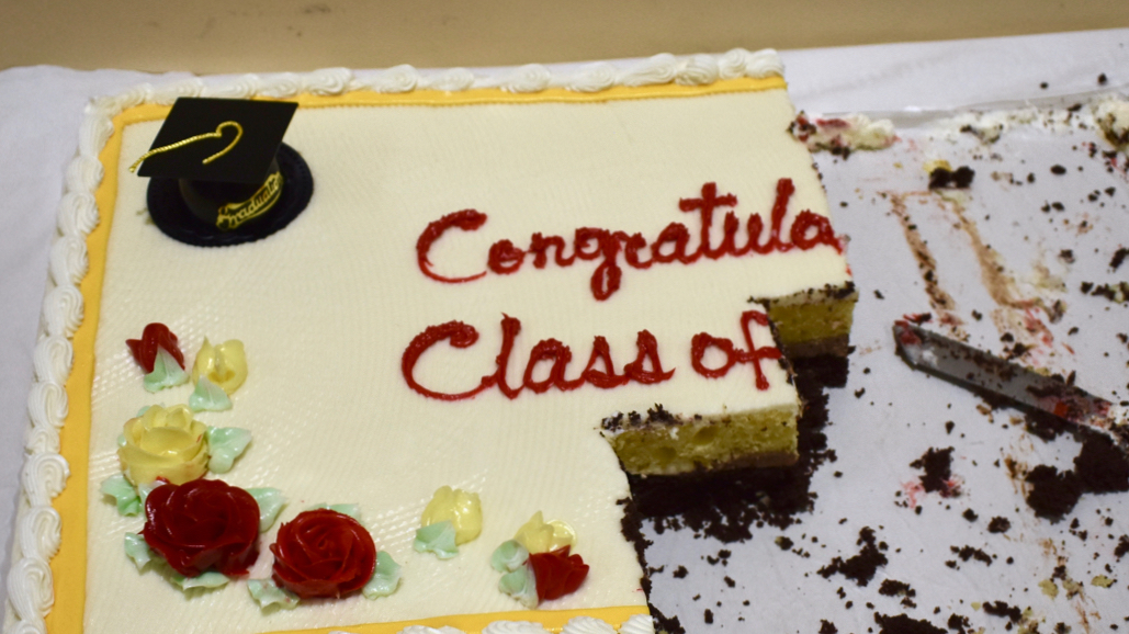 "A half-eaten sheet cake, with the remaining words on top reading: ""Congrat... Class of..."""