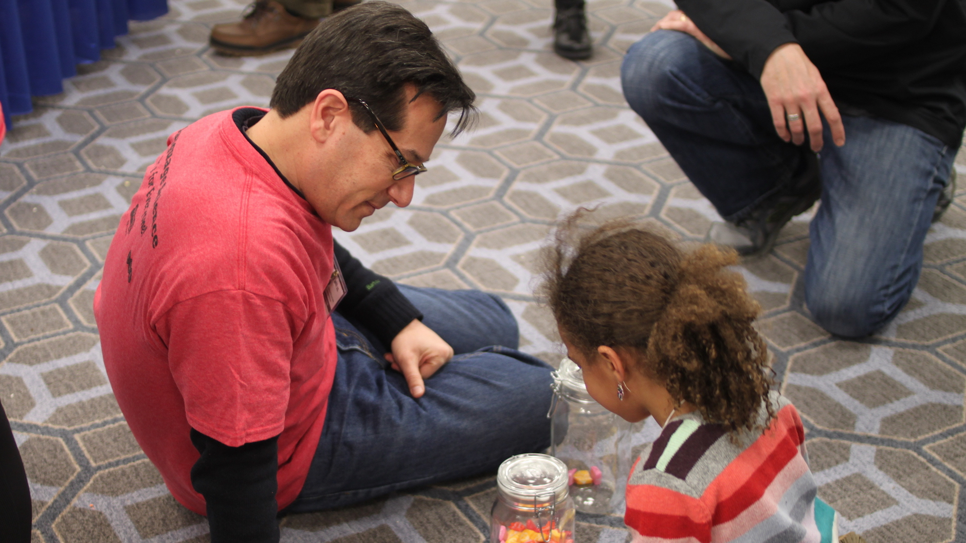 Professor Jeff Lidz, sitting on the floor with a girl, maybe 7 years old, playing games that teach her about the psychology of counting