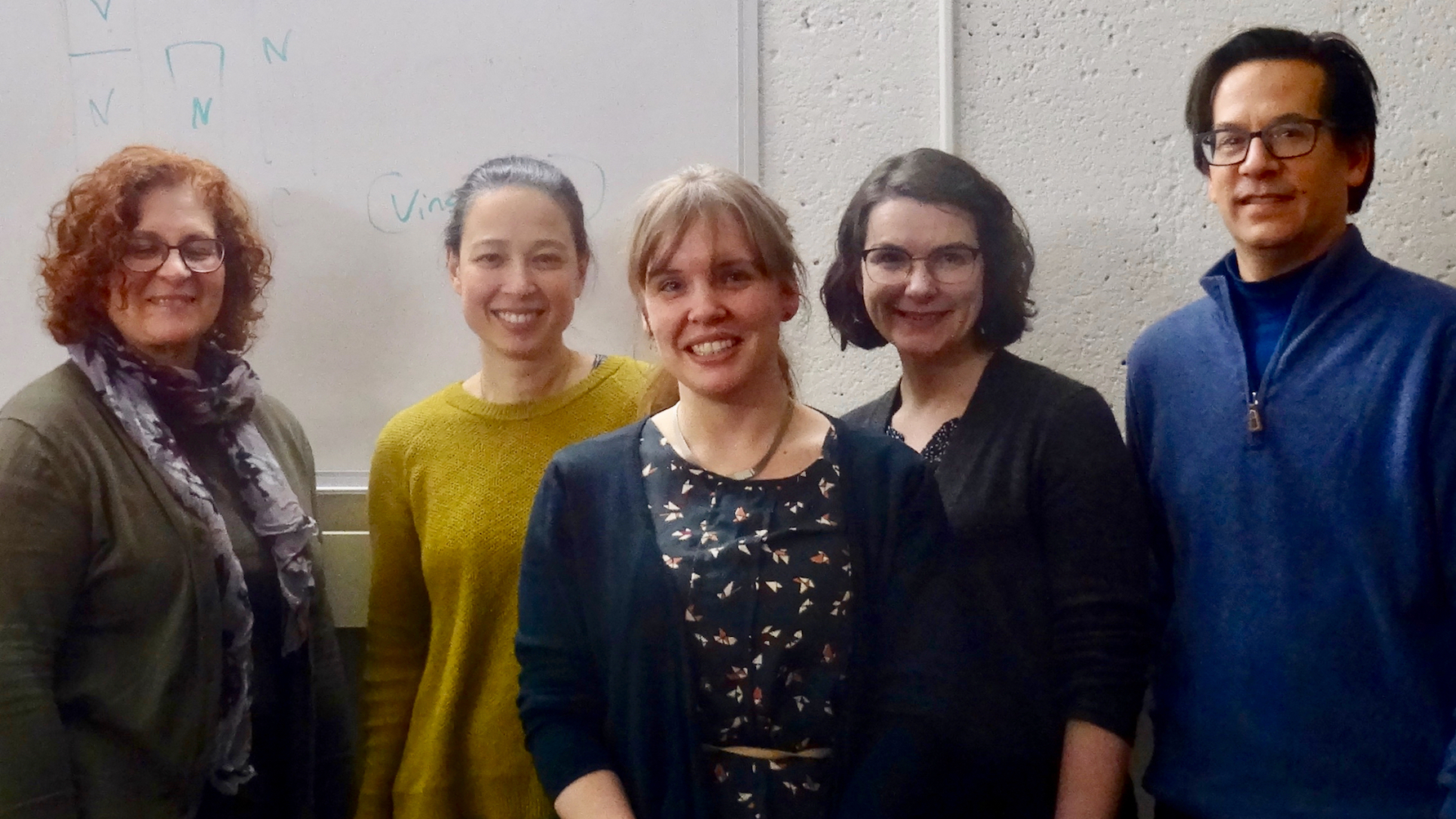 PhD student Annmarie van Dooren, flanked by the members of her qualifying committee, all smiling for the camera in commemoration of a successful oral defense