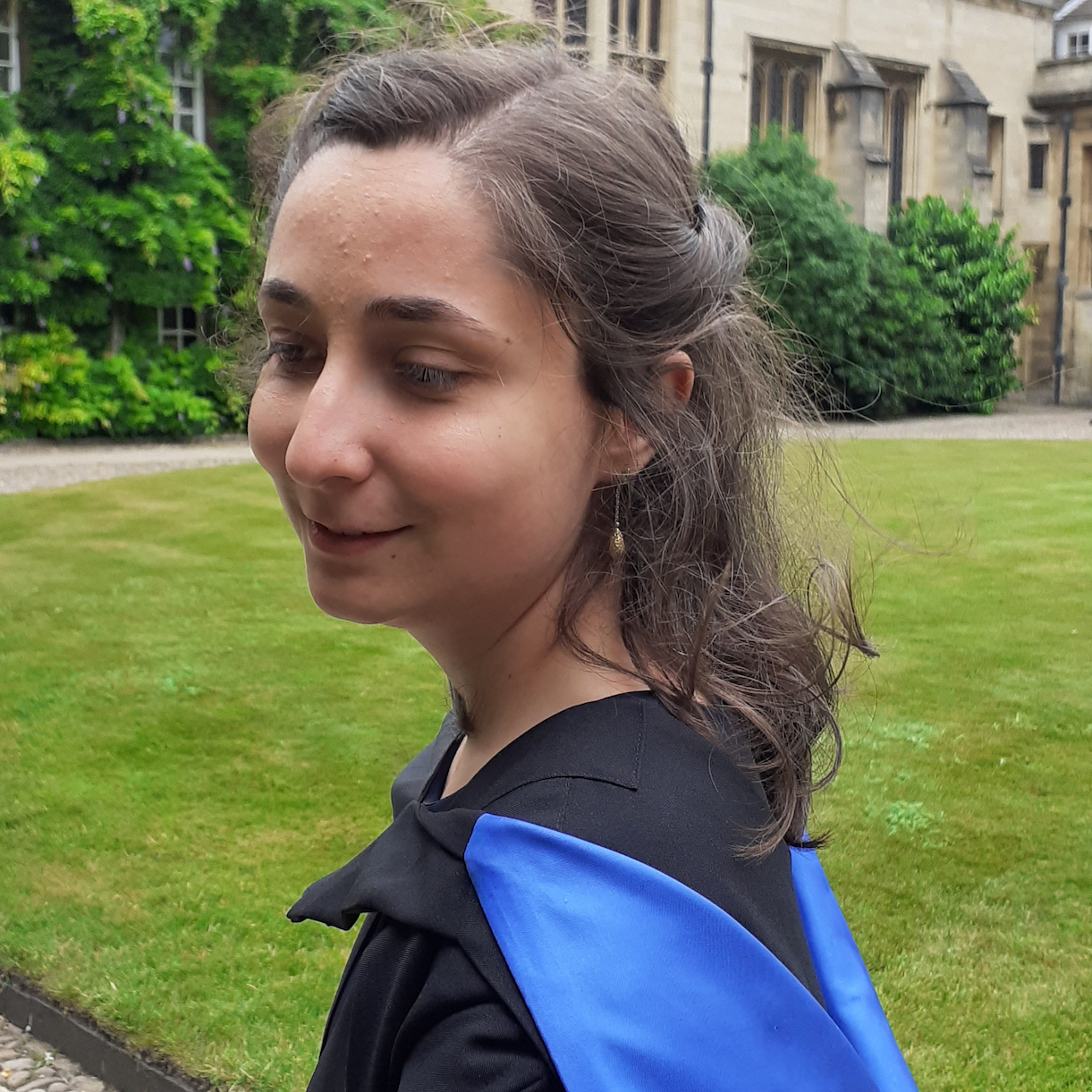 PhD student Clara Cuonzo, in profile, graduation robe visible on her shoulders, standing on a green field of grass at Cambridge University