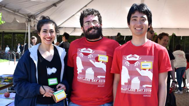 Three Linguistics students, wearing Maryland Day t-shirts, arm in arm and smiling at the camera, doing outreach activities for Maryland Day 2019